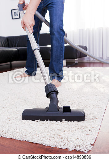 Happy man is cleaning in the modern room with vacuum.