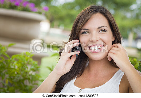 Young Adult Female Talking on Cell Phone Outdoors on Bench - csp14889527