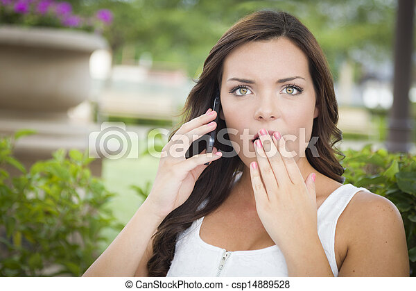 Shocked Young Adult Female Talking on Cell Phone Outdoors - csp14889528