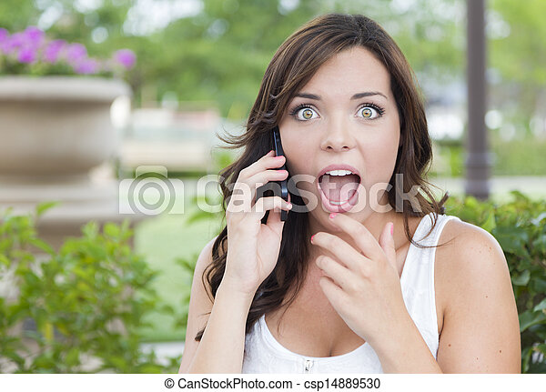Shocked Young Adult Female Talking on Cell Phone Outdoors - csp14889530