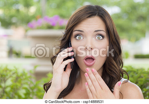 Shocked Young Adult Female Talking on Cell Phone Outdoors - csp14889531