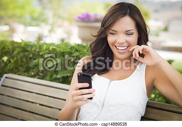 Young Adult Female Texting on Cell Phone Outdoors - csp14889538
