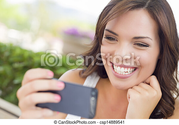 Young Adult Female Texting on Cell Phone Outdoors - csp14889541