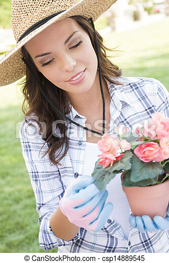 Young Adult Woman Wearing Hat Gardening Outdoors - csp14889545