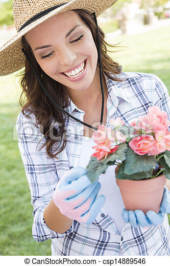 Young Adult Woman Wearing Hat Gardening Outdoors - csp14889546