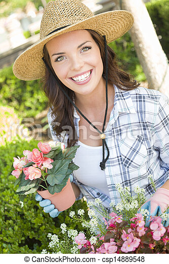 Young Adult Woman Wearing Hat Gardening Outdoors - csp14889548