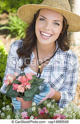 Young Adult Woman Wearing Hat Gardening Outdoors - csp14889549