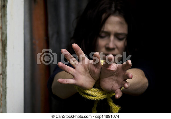Missing kidnapped, abused, hostage, victim woman with hands tied up with rope in emotional stress and pain, afraid, restricted, trapped, call for help, struggle, terrified, locked in a cage cell.