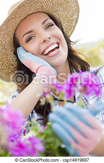 Young Adult Woman Wearing Hat Gardening Outdoors - csp14919697