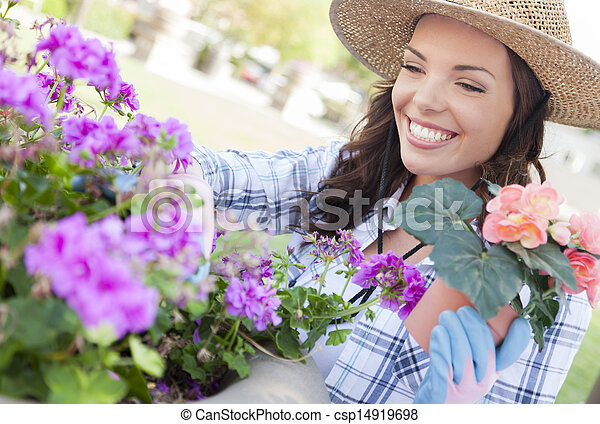 Young Adult Woman Wearing Hat Gardening Outdoors - csp14919698