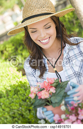 Young Adult Woman Wearing Hat Gardening Outdoors - csp14919701