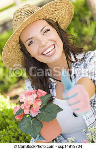 Young Adult Woman Wearing Hat Gardening Outdoors - csp14919704