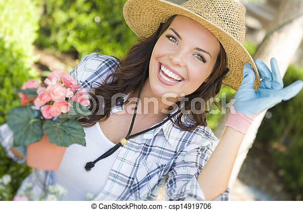 Young Adult Woman Wearing Hat Gardening Outdoors - csp14919706