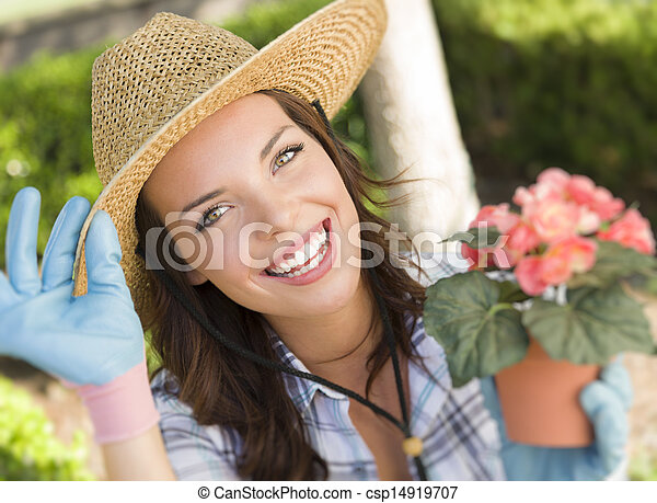 Young Adult Woman Wearing Hat Gardening Outdoors - csp14919707