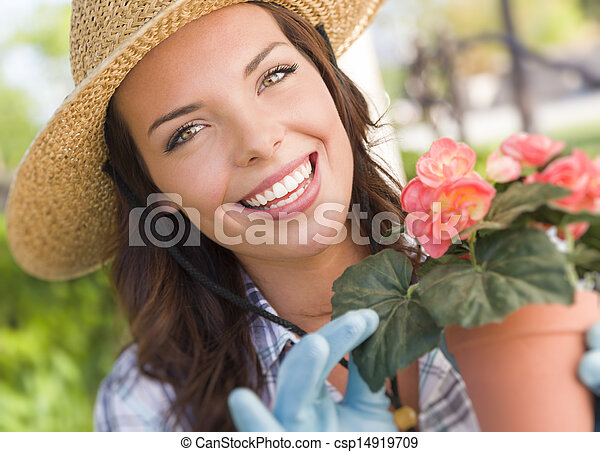 Young Adult Woman Wearing Hat Gardening Outdoors - csp14919709