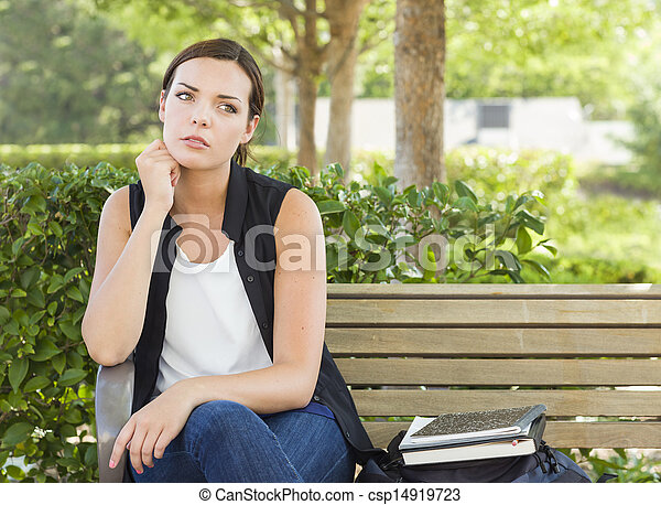 Melancholy Young Adult Woman Sitting on Bench Next to Books  - csp14919723