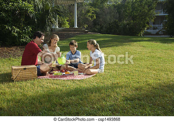 Caucasian family of four having picnic in park.