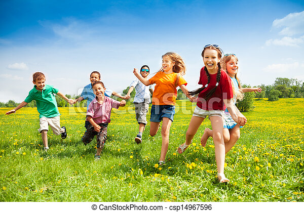Large group of children running in the dandelion spring field