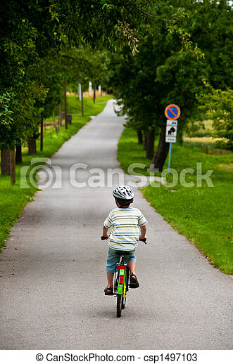 boy riding bicycle on rural road