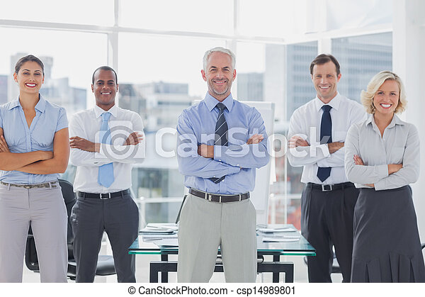 Team of smiling business people standing with arms folded - csp14989801