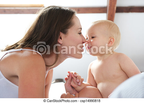 Beautiful woman and baby playing on bed - csp14990818