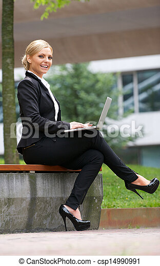Beautiful business woman working with laptop in park - csp14990991
