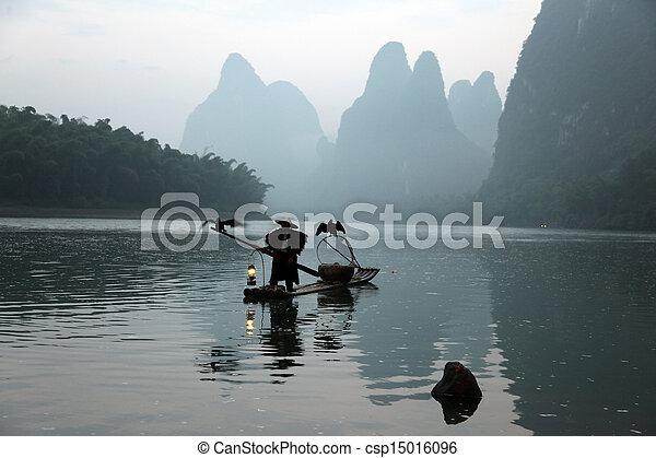 YANGSHUO - JUNE 19: Chinese man fishing with cormorants birds in Yangshuo, Guangxi region, traditional fishing use trained cormorants to fish, June 19, 2012 - csp15016096