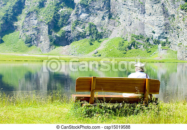 old man sitting on a wooden bench - csp15019588