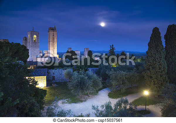 San Gimignano on night, medieval town landmark. Moon light on towers and park with cypress and olive trees. Tuscany, Italy, Europe. - csp15037561
