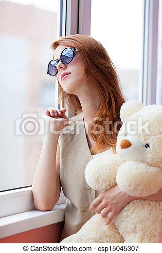 Sad grunge girl near window with toy bear