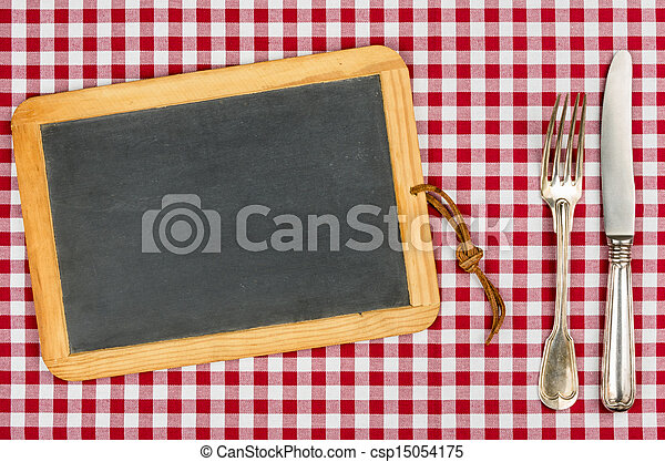 Empty blackboard with silverware on a checkered tablecloth - csp15054175