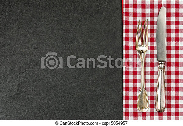 Silverware on a slate plate with a red checkered tablecloth - csp15054957