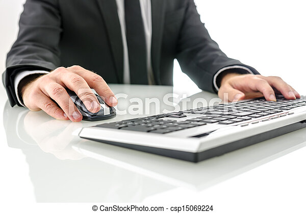 Businessman at office desk working on computer - csp15069224