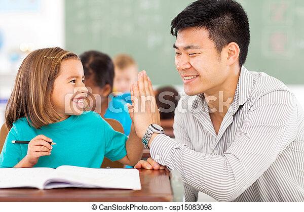 elementary school teacher and student high five - csp15083098