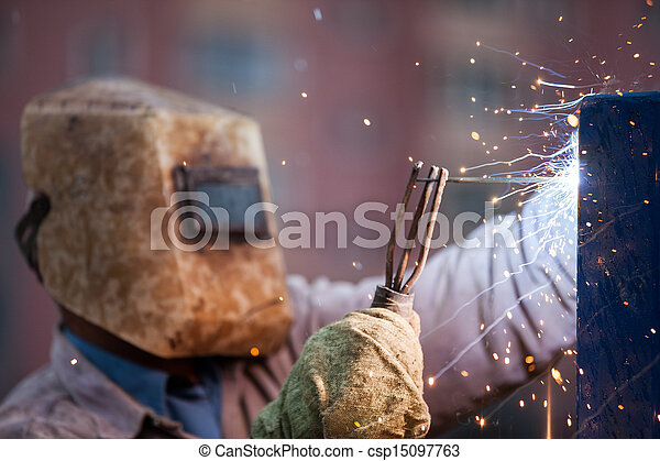 Arc welder worker in protective mask welding metal construction - csp15097763