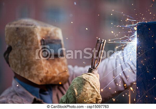 Arc welder worker in protective mask welding metal construction - csp15097763