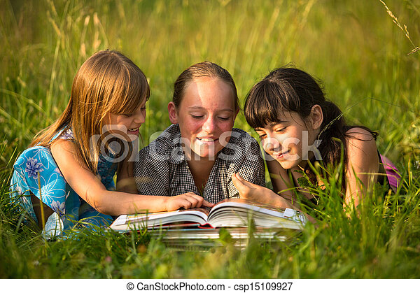 Portrait of cute kids reading book in natural environment together. - csp15109927