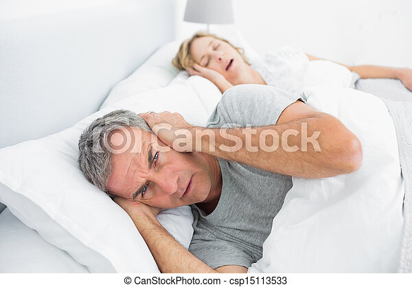 Annoyed man blocking his ears from noise of wife snoring - csp15113533