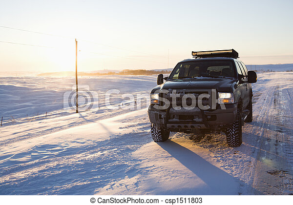 Truck on ice covered road and snowy rural landscape.