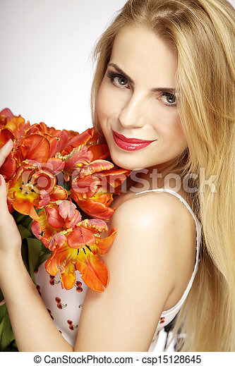 Beautiful and attractive smiling blonde young adult girl with the bouquet of red and yellow tulips flowers isolated on a white background - csp15128645
