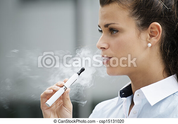 young female smoker smoking e-cigarette outdoors. Head and shoulders, side view - csp15131020