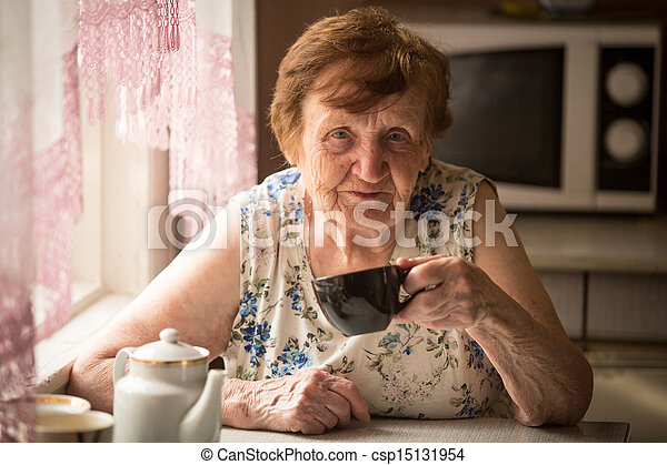 Old woman is drinking tea in his rural home - csp15131954