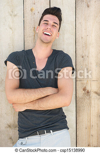 Attractive young man laughing with arms crossed