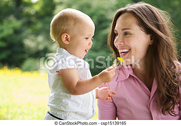 Portrait of a mother and child smiling outdoors - csp15139165