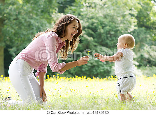 Happy mother teaching baby to walk in the park - csp15139180