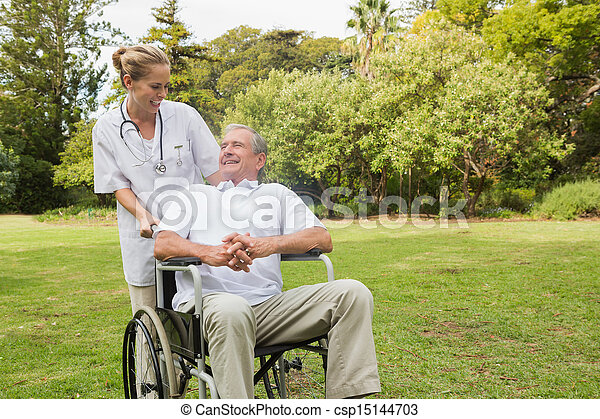 Smiling man sitting in a wheelchair talking with his nurse pushing him at the park - csp15144703