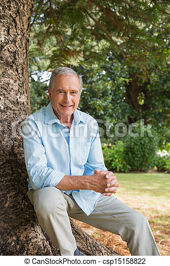 Happy mature man sitting on tree trunk - csp15158822