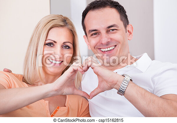 Happy Mid-adult Couple Forming Heart Shape Together - csp15162815
