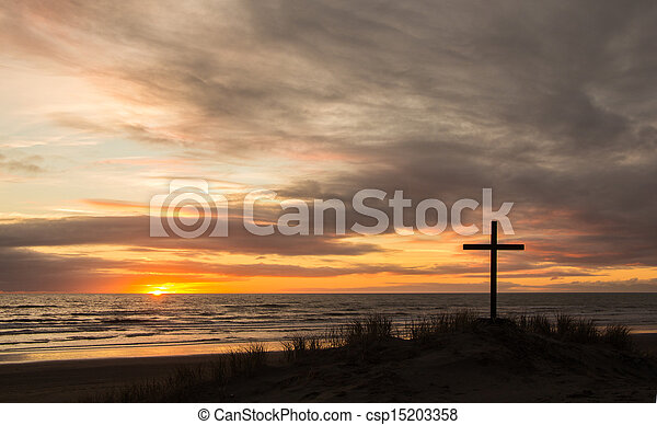 Cross on a sand dune with a wonderful setting sun in the background. - csp15203358