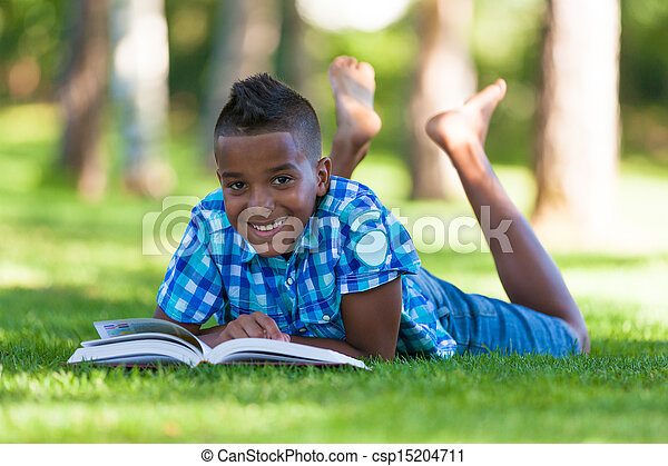 Outdoor portrait of student black boy reading a book - African people - csp15204711